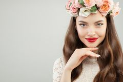 Spring beauty portrait of perfect young model woman. Pretty girl with red lips makeup and flowers wreath smiling.  royalty free stock image
