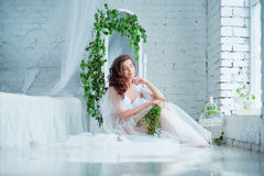Spring beauty. Young beautiful woman sitting near bed in rustic style interior. Royalty Free Stock Image