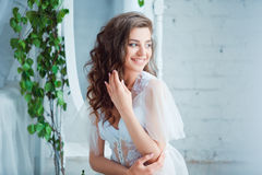Spring beauty. Young smiling beautiful woman sitting in rustic style interior. Stock Photos