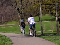 Spring bike ride. Father and daugher riding bicycles in spring royalty free stock image