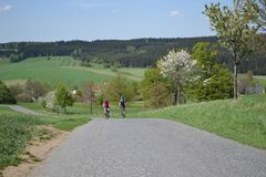 Spring bike riding on the beautiful hills. Young couple on bikes riding on the beautiful green hills during beautiful spring day stock photo