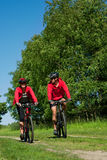 Spring bike - Young sportive couple in meadow Royalty Free Stock Image