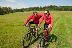 Spring bike - Young sportive couple in meadow. Sportive couple riding mountain bike in summer meadow on a sunny day Royalty Free Stock Photo