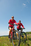 Spring bike - Young sportive couple in meadow. Sportive couple riding mountain bike in summer meadow on a sunny day Stock Photo