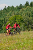 Spring bike - Young sportive couple in meadow Stock Images