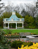 Spring Botanical Garden with Victorian Gazebo. A garden setting with a beautiful Victorian gazebo, bright colorful tulips, and welcoming park benches during Stock Photo