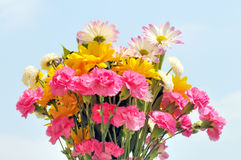 Spring bouquet. A closeup view of a colorful, cheerful bouquet of fresh spring flowers including daisies and carnations against a light blue sky Stock Photos