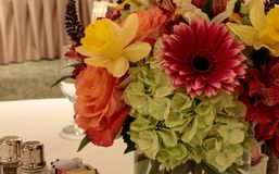 Spring bouquet of pink Gerbera daisies, yellow daffodils, orange roses, and green hydrangea. On a linen dinner table setting stock photography