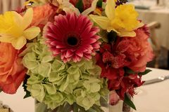 Spring bouquet of pink Gerbera daisies, yellow daffodils, orange roses, and green hydrangea. On a linen dinner table setting stock photos