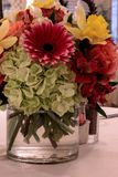 Spring bouquet of pink Gerbera daisies, yellow daffodils, orange roses, and green hydrangea. On a linen dinner table setting royalty free stock photos