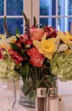 Spring bouquet of pink Gerbera daisies, yellow daffodils, orange roses, and green hydrangea. On a linen dinner table setting stock photo