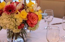 Spring bouquet of pink Gerbera daisies, yellow daffodils, orange roses, and green hydrangea. On a linen dinner table setting stock images