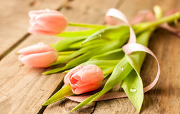 Spring bouquet of pink tulips on vintage wood Stock Photos