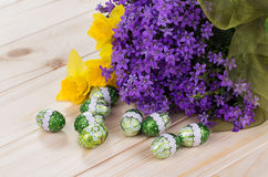 Spring bouquet of purple flowers and daffodils with chocolate eggs on a light wooden background Royalty Free Stock Images