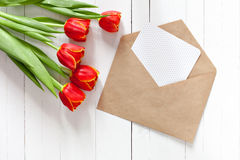 Spring bouquet of red tulips and a card in an envelope Stock Photos