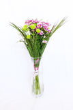 Spring Bouquet in a Vase. Bouquet of yellow, violet and white flowers in a transparent glass vase isolated on white Royalty Free Stock Photo