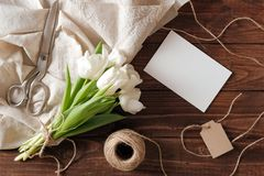 Spring bouquet of white tulip flowers, blank paper card, scissors, twine on rustic wooden desk. Womens day composition on flat lay royalty free stock images