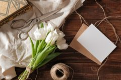 Spring bouquet of white tulip flowers, blank paper card, scissors, twine on rustic wooden desk. Womens day composition on flat lay stock image