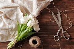 Spring bouquet of white tulip flowers, blank paper card, scissors, twine on rustic wooden desk. Womens day composition on flat lay royalty free stock photos