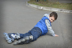 Spring boy rollerblading and fell on the road. Royalty Free Stock Image