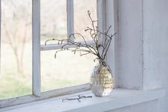 Spring branches in vase on windowsill. Spring branches in vase on white old windowsill royalty free stock photos
