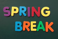 Spring break. Several bold multicolored letters build the term spring break on a blackboard royalty free stock image