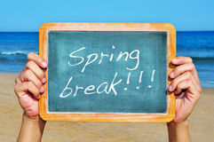 Spring break. Someone holding a blank blackboard at the beach with the sentence spring break written in it Royalty Free Stock Image