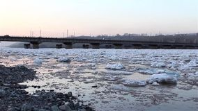 Spring break, floating, drifting, ice on the river against the background of the road bridge view from the shore stock footage