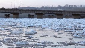 Spring break, floating, drifting, ice on the river against the background of the road bridge view from the shore. Background noise, splash, birds singing HD stock video