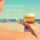Spring break, here we go. The text spring break, here we go written on a blurred image of a young man having a beer on the beach stock images
