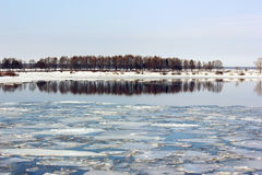 Spring break on the river. The ice on the surface of the water. The reflection of the shore with trees Royalty Free Stock Images