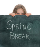 Spring Break. Schoolgirl hiding behind blackboard with Spring Break text Stock Photo