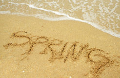 Spring break. A warm tropical beach for spring break concept and spring written in the sand stock photos