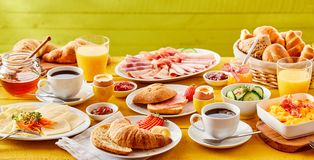 Spring breakfast banner with a choice of foods. Including a croissant, am or bacon roll, omelette, cold meat cuts, cheese, honey and jams served with orange Stock Photo