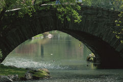 Spring bridge. Stone arched bridge over pond in central park with ducks and spring colors reflected Royalty Free Stock Photo