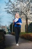 Spring always brings some good news. Young beautiful blonde female postman in blue shirt and black jeans goes with letters with a smile and grace through stock photo