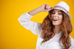 Spring brunette girl with hat in a yellow background Royalty Free Stock Photography