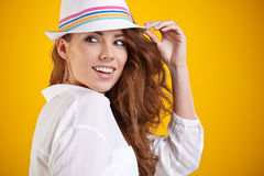 Spring brunette girl with hat in a yellow background Royalty Free Stock Images