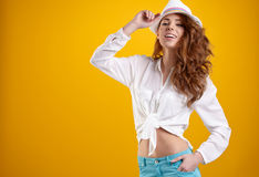 Spring brunette girl with hat in a yellow background Stock Image