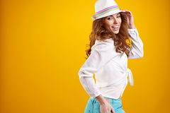 Spring brunette girl with hat in a yellow background Stock Images