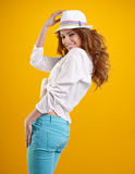 Spring brunette girl with hat in a yellow background Royalty Free Stock Photo
