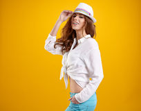 Spring brunette girl with hat in a yellow background Stock Photo