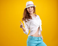 Spring brunette girl with hat in a yellow background Royalty Free Stock Image