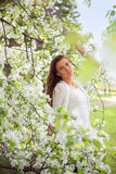 Spring brunette girl standing outdoor in blooming trees. Beautif Royalty Free Stock Images