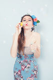 Spring bubble. Young lady with a circlet made of flowers blowing soap bubbles on blue background Royalty Free Stock Photography