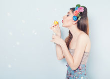Spring bubbles. Profile of a young beautiful lady blowing soap bubbles on blue background Stock Photography