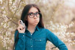 Allergic Woman with Asthmatic Symptoms Holding Asthma Inhaler Spray. Spring causing health problems for young girl outdoors in blooming nature stock image