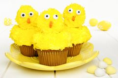 Spring chick cupcakes on yellow plate with Easter eggs Royalty Free Stock Photography