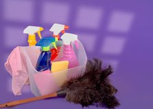 Cleaning Supplies Against A Purple Background. Cleaning supplies for spring with a feather duster and sunlight coming in from a distant window Royalty Free Stock Photo