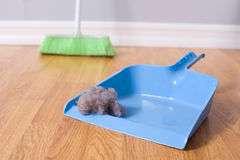 Spring Cleaning. Sweeping large dust bunny on a hardwood floor royalty free stock photography